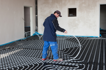 Man installing underfloor heating pipes in new build house